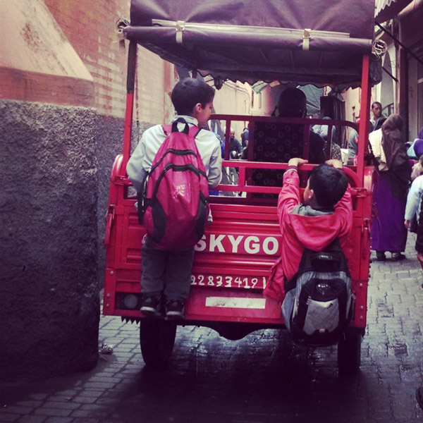 Kids hitching a ride through Marrakech